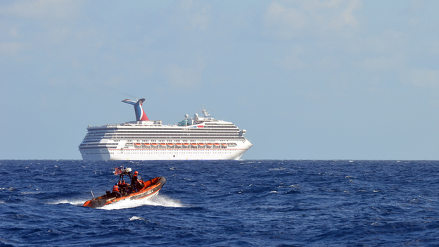 Coast Guard patrols near the cruise ship Carnival Triumph in the Gulf of Mexico on Monday. The Carnival Triumph lost propulsion power after an engine room fire a day earlier. (AFP/Getty Images)
