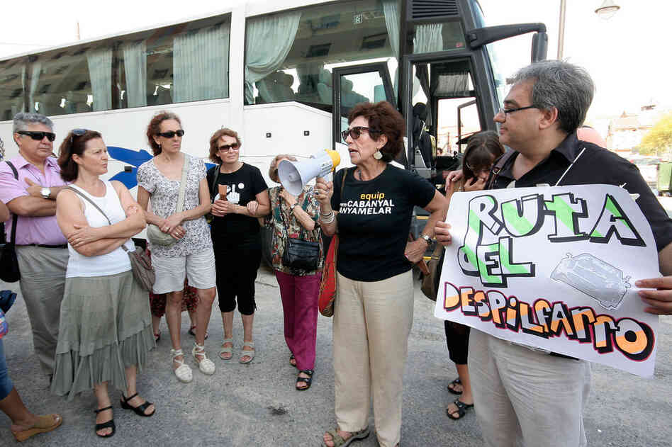 "Miguel Angel Ferris Gil (right) holds a sign reading ""Route of Wastefulness"" during one of his tours of Valencia's landmarks."