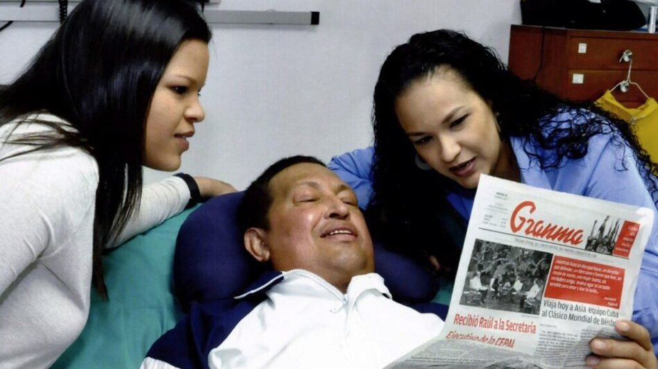 A handout picture made available Friday by the Venezuelan Ministry of Communications and Information shows Venezuelan President Hugo Chavez and his daughters  Rosa Virginia (right) and Maria Gabriela reading an edition of Cuban daily <em>Granma</em>, as he recovers from cancer surgery. It was reportedly taken on Thursday.