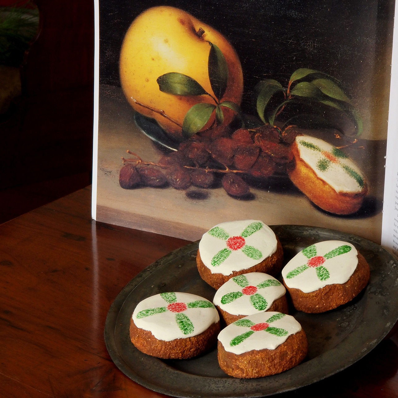 Cakes displayed with a reproduction of Raphaelle Peale's Still Life with Cake, from circa 1822