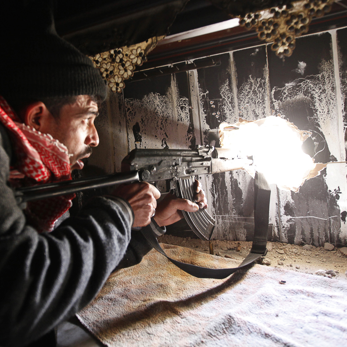 A Free Syrian Army fighter takes up position inside a burnt room in Aleppo on Nov. 12, 2012.