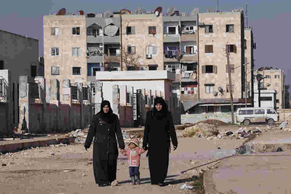 Women holding a child's hands walk along a street in Aleppo's Hanano district in January.