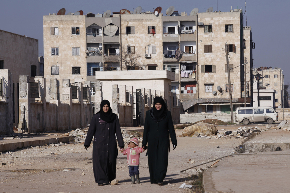 Women holding a child's hands walk along a street in Aleppo's Hanano district in January.  (Reuters via Landov)