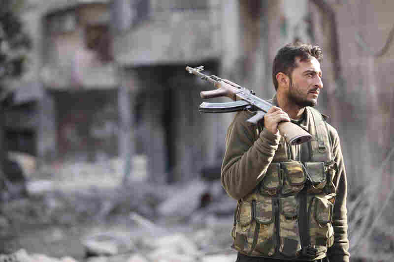 A Free Syrian Army fighter stands on a damaged street in Aleppo in November.