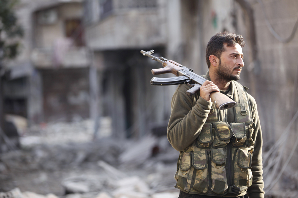 A Free Syrian Army fighter stands on a damaged street in Aleppo in November. (Reuters via Landov)