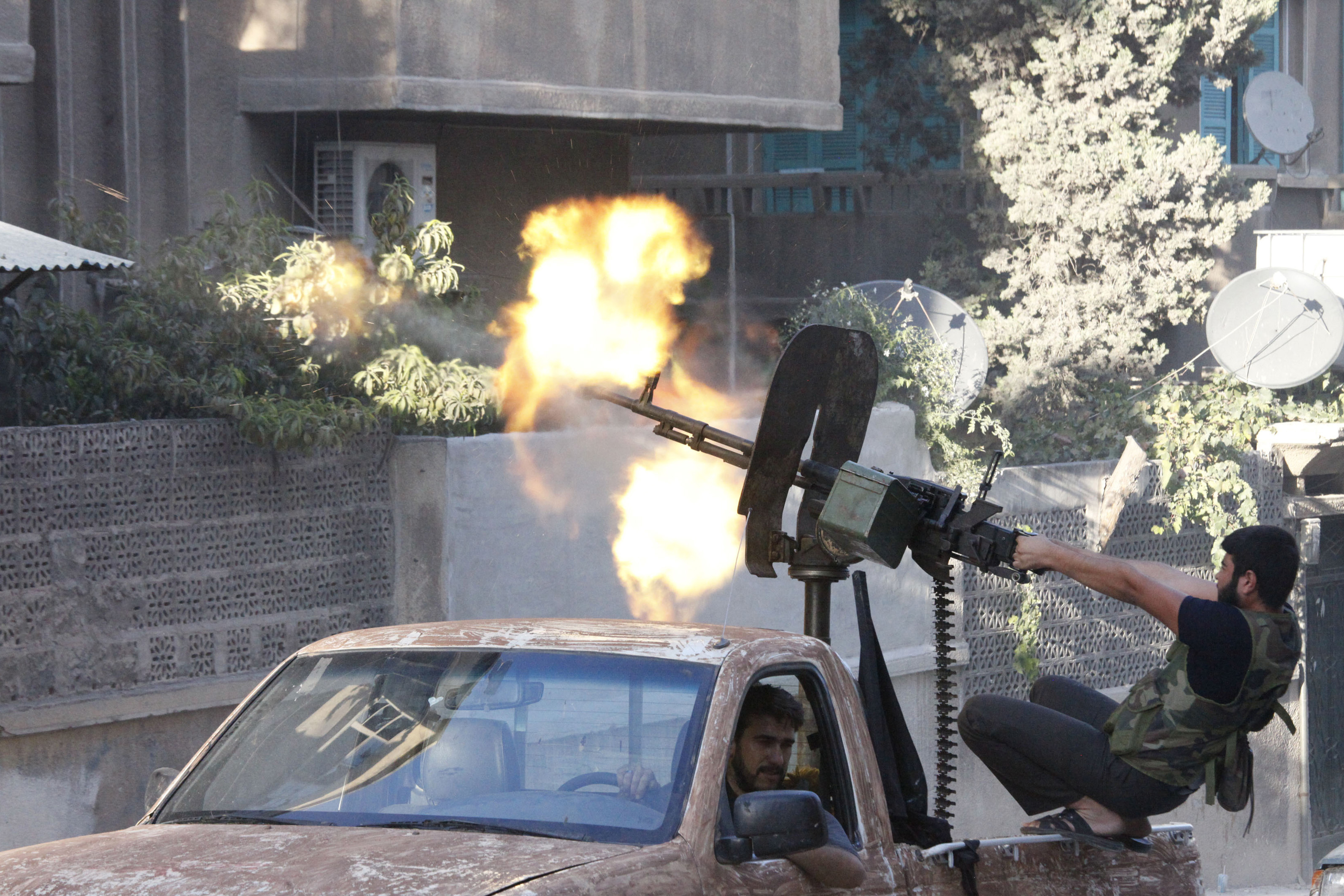 A member of the Free Syrian Army opens fire with a machine gun during clashes with Syrian army forces in Aleppo in September.