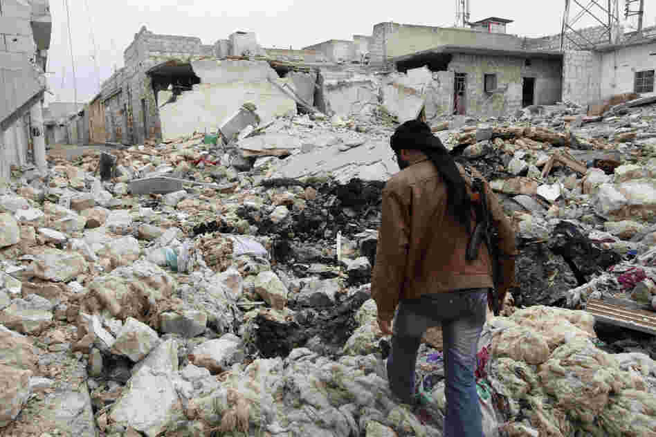 A Free Syrian Army fighter walks among the rubble of damaged buildings near a cement factory in Aleppo earlier this month.