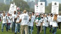 Rami Nashashibi, fourth from left, claps as he marches with IMAN leaders during a May Day immigration rally in Chicago in 2007.