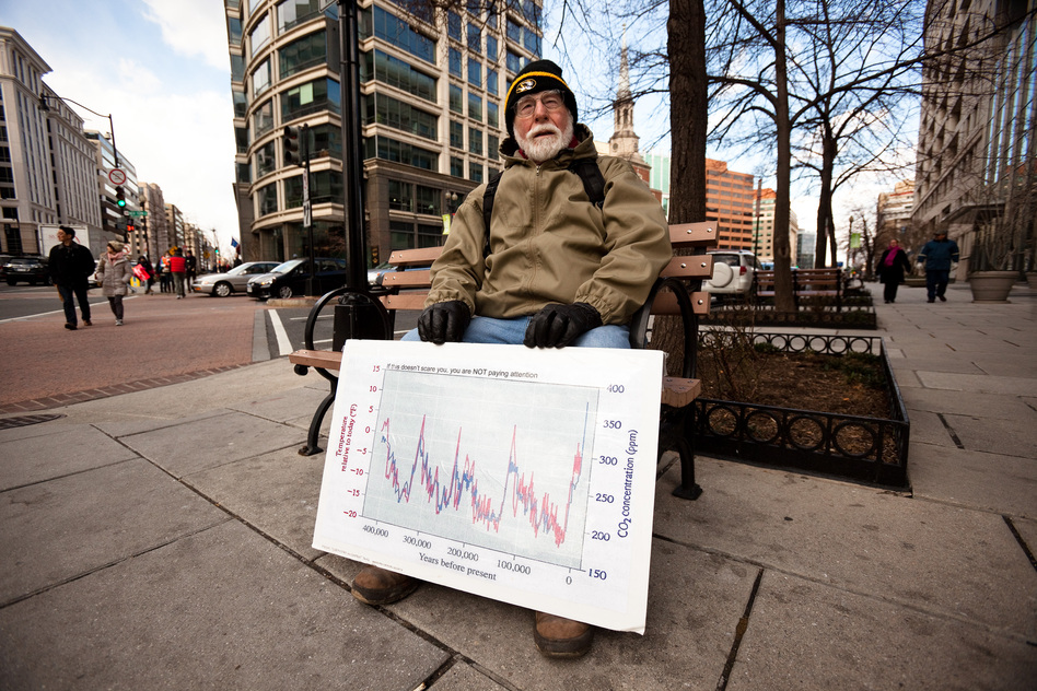Dr. J. William Hirzy, a chemistry professor at American Universiy, rests outside the rally route with a graph he uses to teach his students about the relationship between atmospheric carbon dioxide and global temperature. (NPR)