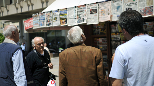 People read newspaper headlines in Athens. In 2009, there were 39 national dailies, 23 national Sunday papers, 14 national weekly papers and dozens of TV and radio stations for a population of 11 million. (AFP/Getty Images)