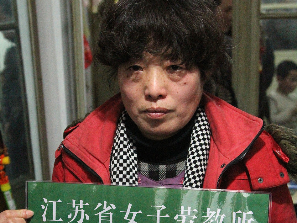 Tang Shuxiu, 51, was sent to a re-education through labor camp in 2011 after she complained that her local government work unit failed to give her an apartment. She holds a mock-up of her labor camp ID card in order to publicize the abuses of labor camps and push for change.
