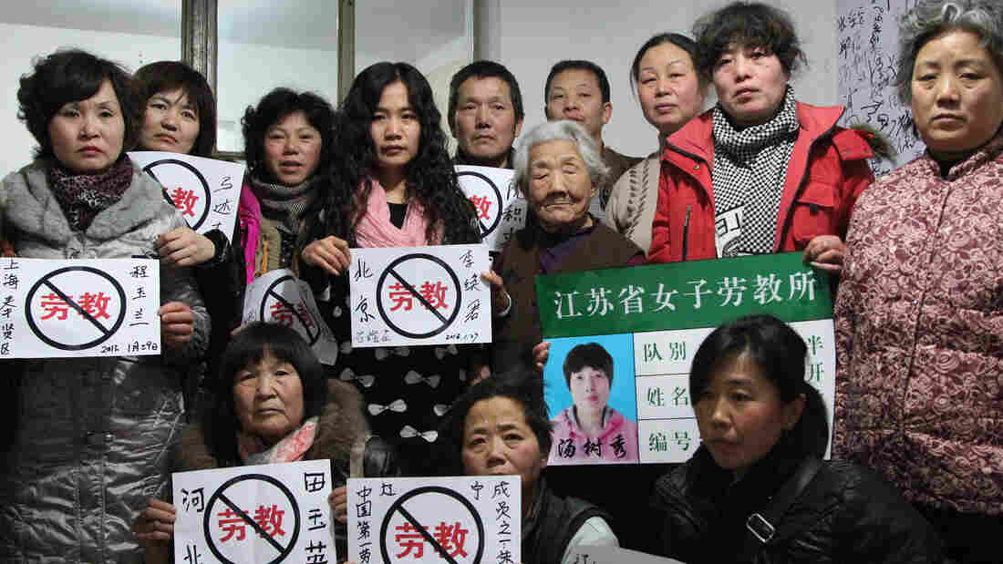 "Some former prisoners of re-education through labor camps and their supporters hold signs in Beijing declaring, ""No Re-education Through Labor."" Popular opposition to the camps has grown as China's state-run media has highlighted particularly egregious cases."