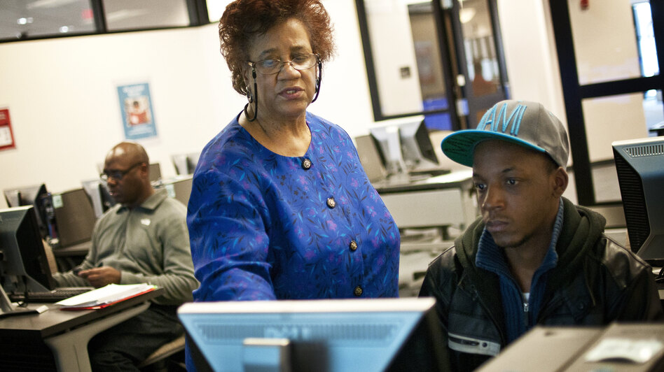 Part-time librarian Janet Sims-Wood, 67, helps student Andre Williams navigate the online catalogue at the Accokeek Library at Prince George's Community College in Largo, Md. (NPR)