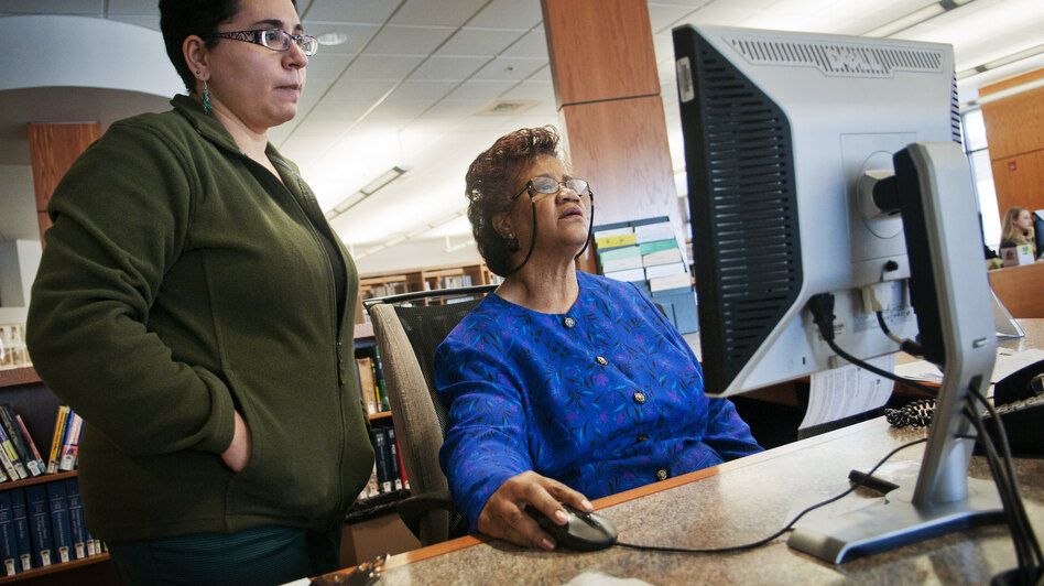 "Sims-Wood goes over computer data with librarian Maria Bonet. Though Sims-Wood is on the job at a time when she thought she would be retired, she stays positive. ""I have faith that things will work out. I don't care how bad they are. It's going to work out,"" she says. (NPR)"