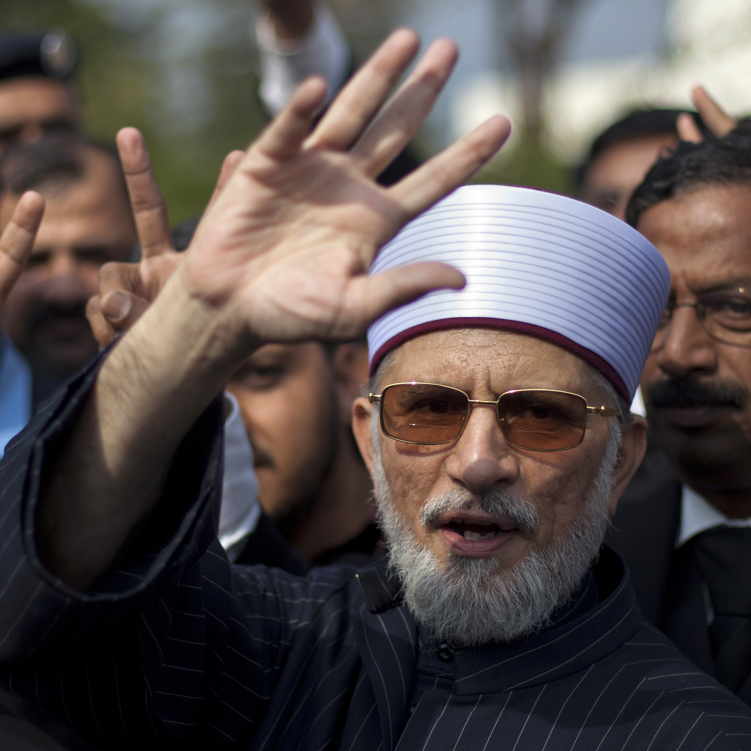 Tahirul Qadri, a dual national of Pakistan and Canada, waves to his supporters as he leaves the Supreme Court in Islamabad, Pakistan on Feb. 12, 2013.