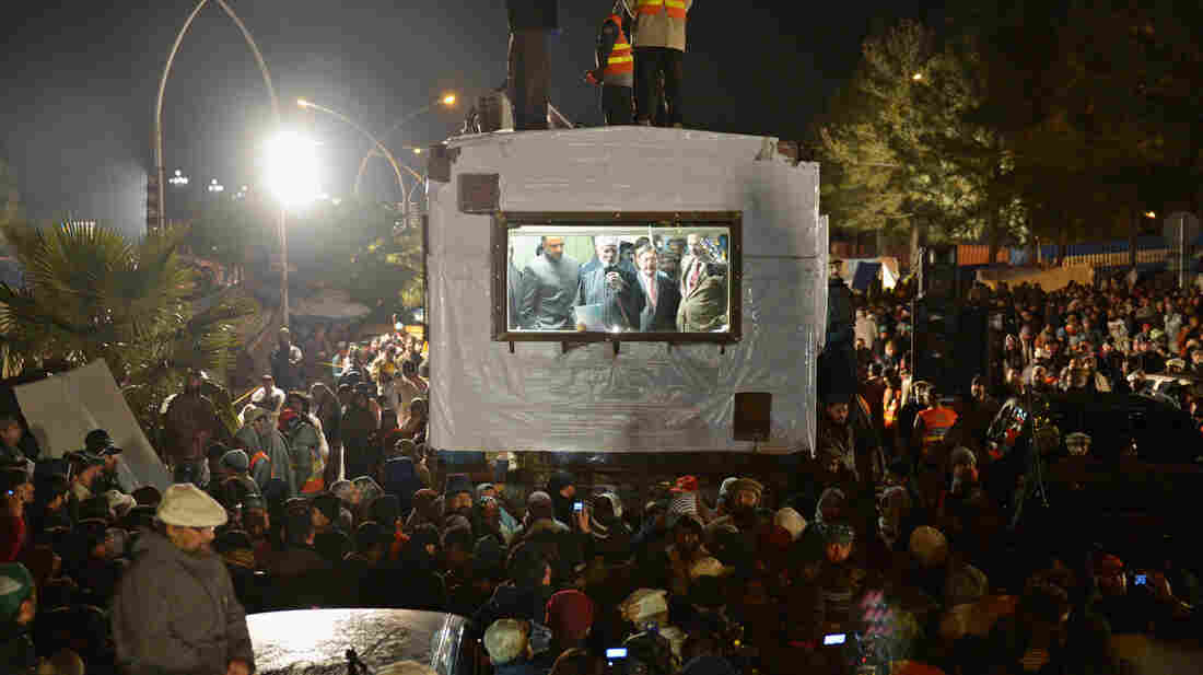 Pakistani Muslim cleric Tahir-ul-Qadri (center), speaks to a crowd from a bulletproof box in Islamabad in January. The cleric recently returned to Pakistan after years in Canada, and his calls for an end to corruption have brought supporters to the streets in large numbers.