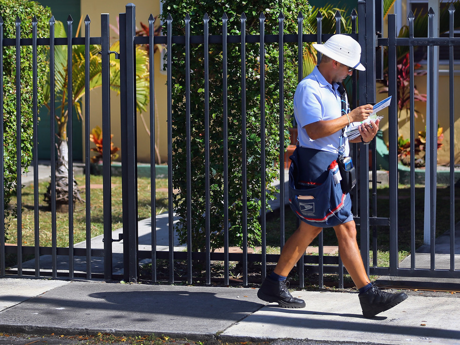 A mailman for the U.S. Postal Service delivers mail on November 15, 2012 in Miami, Florida.