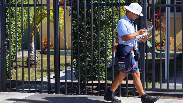 A mailman for the U.S. Postal Service delivers mail on November 15, 2012 in Miami, Florida. (Getty Images)