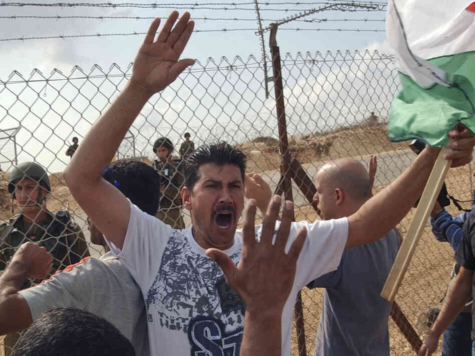 With Israeli soldiers on the other side, Palestinians protest against Israel's West Bank separation barrier in the town of Bil'in in 2008.