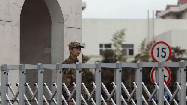 A Chinese soldier stands guard Tuesday in front of the Shanghai building that houses military Unit 61398. A U.S. cybersecurity company says the unit is behind nearly 150 computer attacks on U.S. and other Western companies and organizations in recent years. China denies the allegation. (Reuters/Landov)