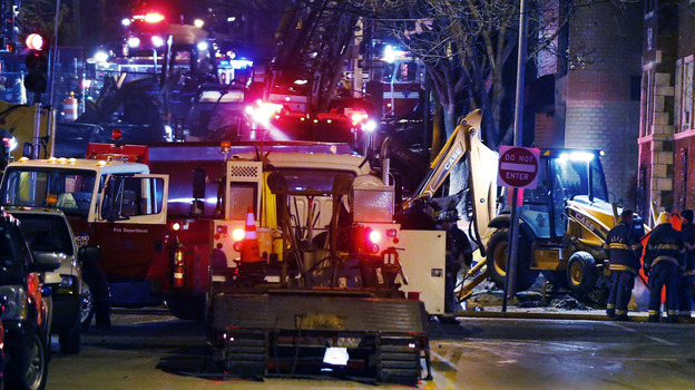 Fire fighters and utility workers at the scene of a massive gas explosion and fire Tuesday night in Kansas City, Mo. (AP)