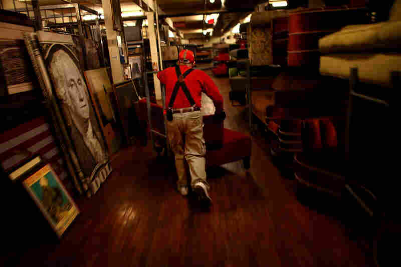 "Warner Brothers worker Stephen Lampke moves furniture on the Prop House's second floor, which holds the ""contemporary"" items: sofas, coffee tables, end tables, bookcases, mostly middle-class workaday furniture."