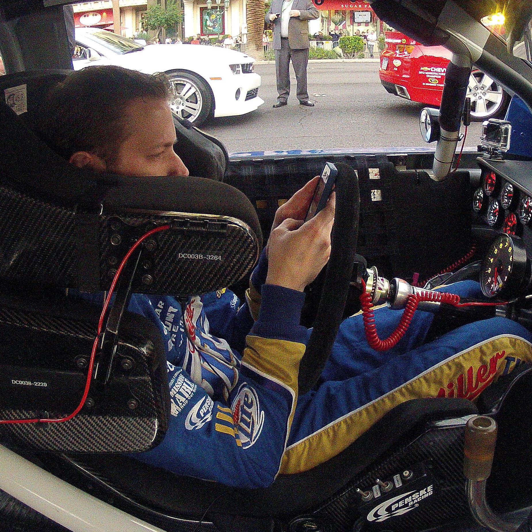 Brad Keselowski looks at his smartphone during a NASCAR champions parade in Las Vegas in November.