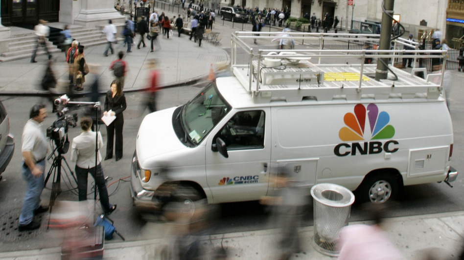 Morning rush hour commuters pass by a CNBC crew in front of the New York Stock Exchange in September 2006. The channel has adopted a policy that prohibits guests from appearing on rival channels amid breaking news. (AP)