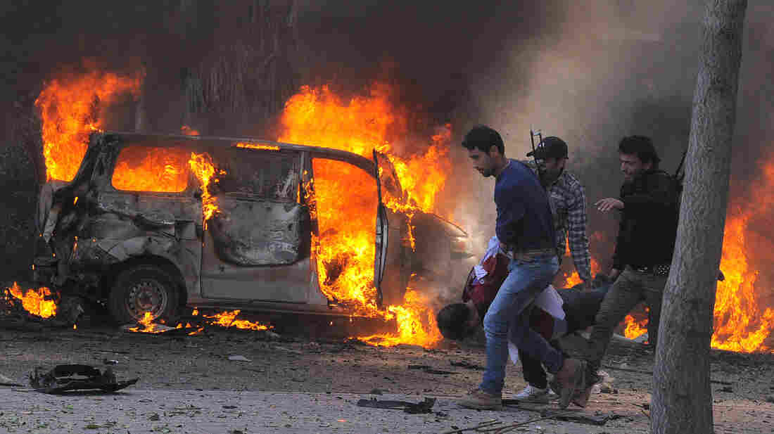 Syrian security agents carry a body following a huge car bombing in Damascus on Thursday. More than 50 people were killed in one o
