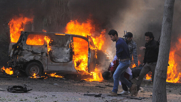 Syrian security agents carry a body following a huge car bombing in Damascus on Thursday. More than 50 people were killed in one of the worst attacks in the capital since the uprising began in 2011.