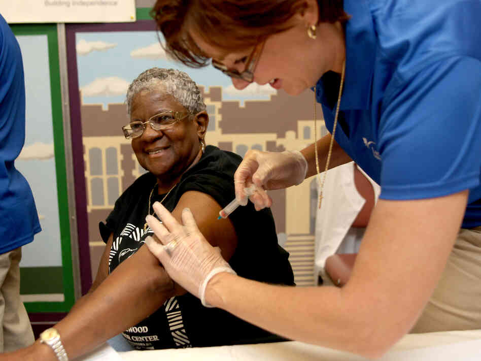 Kimberly Delp gives a flu shot to Carleen Matthews at the Homewood Senior Center in  Pittsburgh,