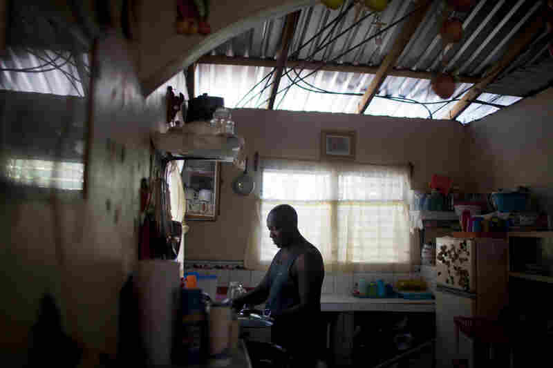 Santos Anael Martinez cooks food in his home Jan. 13 in Sambo Creek. Santos,a fisherman, is HIV-positive; his wife is a community health worker who visits people living with HIV.