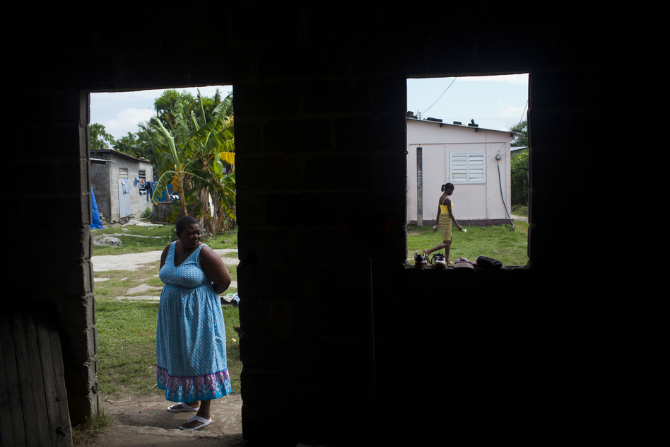 Anatolia Ramirez waits outside the home of one of the HIV-positive women she visits in Sambo Creek. Ramirez is a community health worker who visits people with HIV in order to check up on them, and to offer assistance and support. (Pulitzer Center)