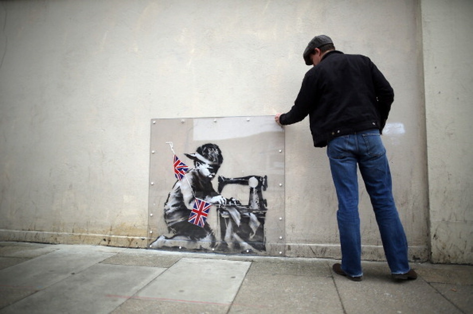 A man inspects a plastic cover placed over an artwork attributed to Banksy in London, England. The stencilled image depicts a poor child making Union Jack flags on a sewing machine and is located on the wall of a Poundland discount shop in the Wood Green area of north London.