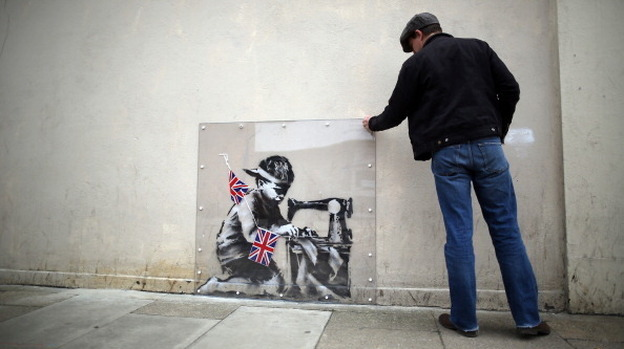 A man inspects a plastic cover placed over an artwork attributed to Banksy in London, England. The stencilled image depicts a poor child making Union Jack flags on a sewing machine and is located on the wall of a Poundland discount shop in the Wood Green area of north London. (Getty Images)