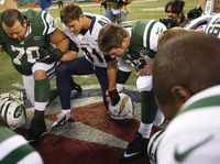 Tim Tebow, center, leads a prayer after the Jets' loss to San Diego Chargers on December 23.