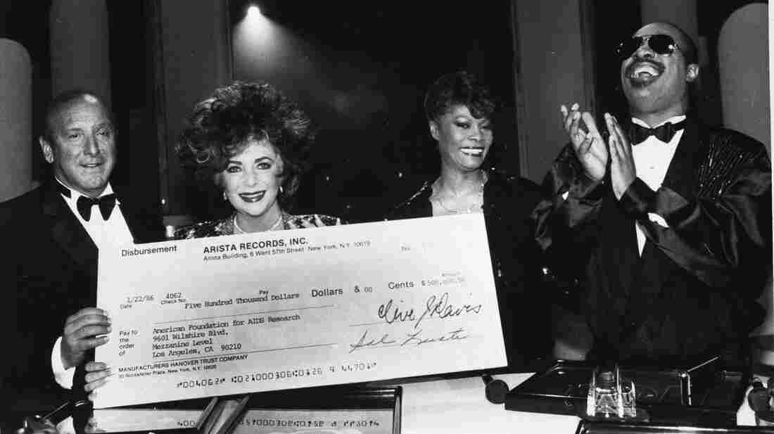 Clive Davis displays a $500,000 check with Elizabeth Taylor, Dionne Warwick and Stevie Wonder at a charity event in Holywood in 1986.