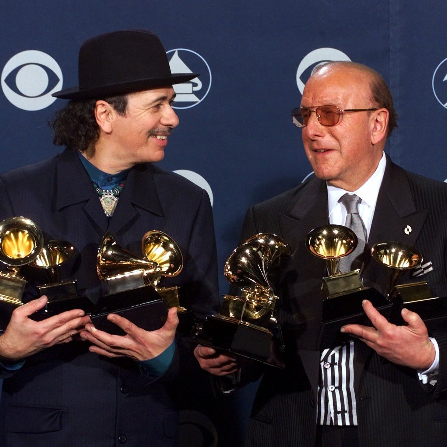 Davis and Carlos Santana pose with the musician's record-tying eight Grammys in Los Angeles in 2000.
