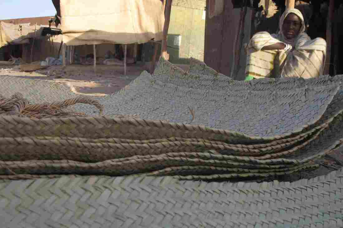 In this Wednesday, Feb. 20, 2013 photo, a young vendor waits for clients alongside woven reed mats of the type purchased by fleeing Islamists, apparently to camouflage their vehicles, in Timbuktu, Mali.