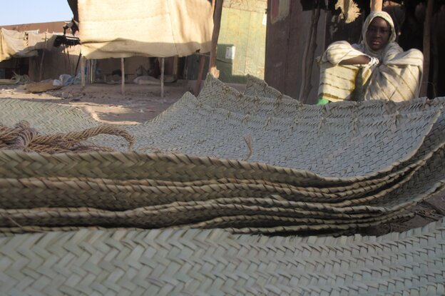 In this Wednesday, Feb. 20, 2013 photo, a young vendor waits for clients alongside woven reed mats of the type purchased by fleeing Islamists, apparently to camouflage their vehicles, in Timbukt