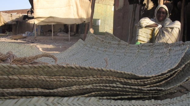 In this Wednesday, Feb. 20, 2013 photo, a young vendor waits for clients alongside woven reed mats of the type purchased by fleeing Islamists, apparently to camouflage their vehicles, in Timbuktu, Mali. (AP)