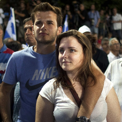 A young couple is framed by Greek flags while watching Antonis Samaras, now the country's prime minister, speak at a campaign rally last June. Samaras wants to dismantle a law making it easier for second-generation Greeks to obtain citizenship.