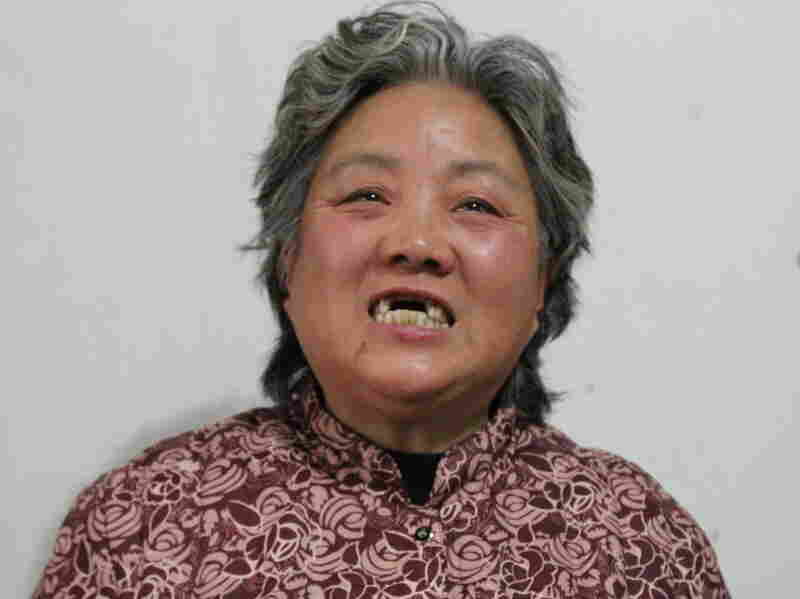 """Shen Lixiu, 58, says she had her front teeth kicked out in a re-education through labor camp. Chinese authorities say they are considering """"reforms"""" to a system that is coming under increasing public criticism."""