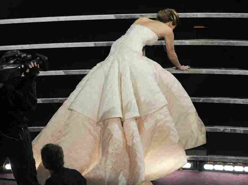 Actress Jennifer Lawrence stumbles as she walks on stage.