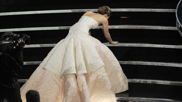 Actress Jennifer Lawrence stumbles as she walks on stage. (AP)