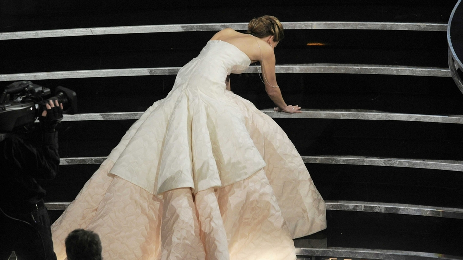 Actress Jennifer Lawrence stumbles as she walks on stage. (AP)
