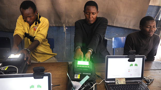 Kenyan authorities are trying to guard against fraud and violence when they hold a presidential election on March 4. Here, voters register on biometric equipment last December in Nairobi. (AFP/Getty Images)