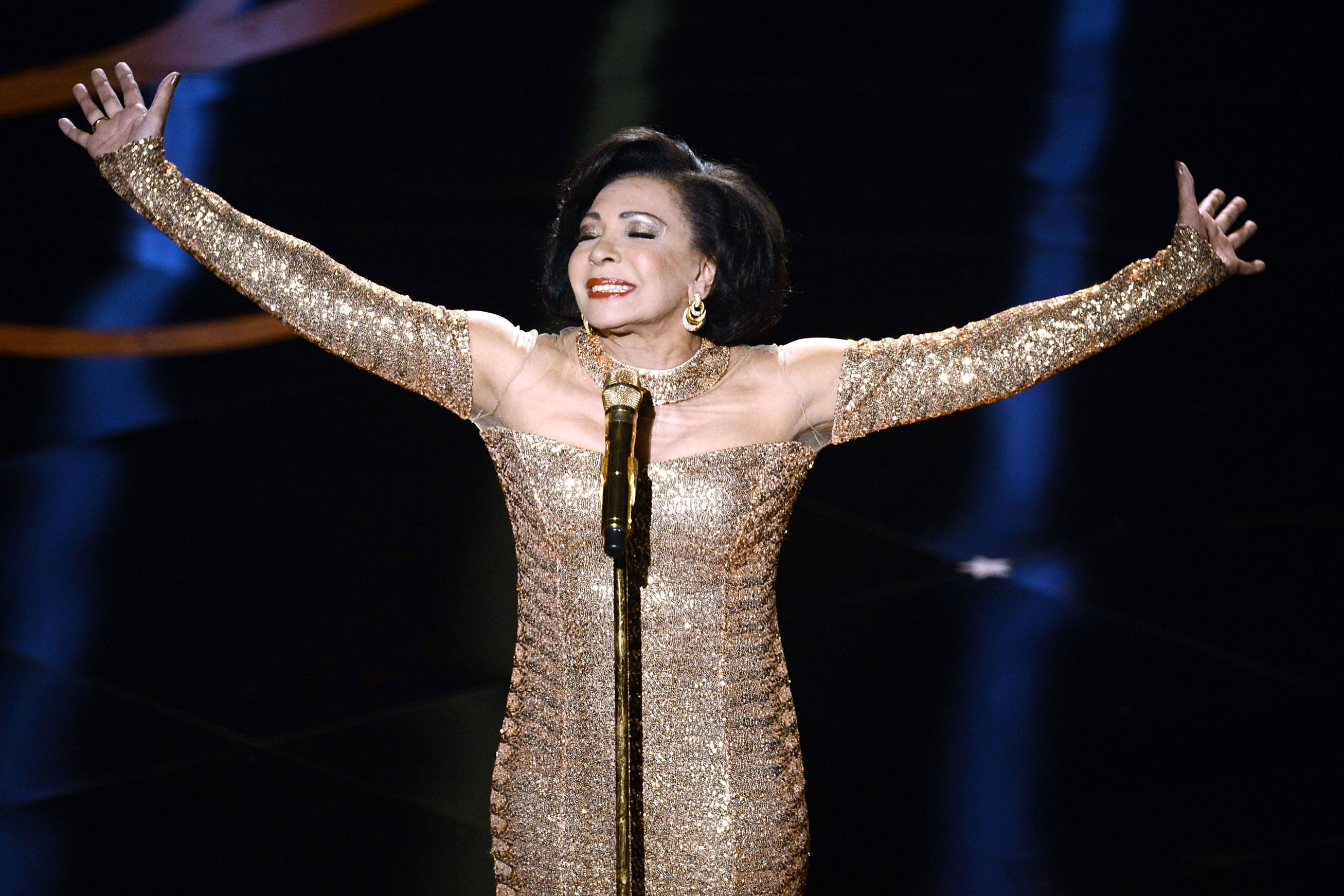 "The legendary Shirley Bassey makes an appearance to sing the theme song from the James Bond classic ""Goldfinger."""