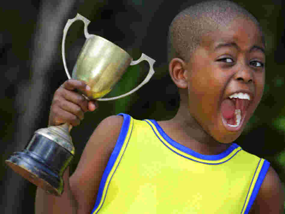 A young child shouts with joy after winning his sporting event.
