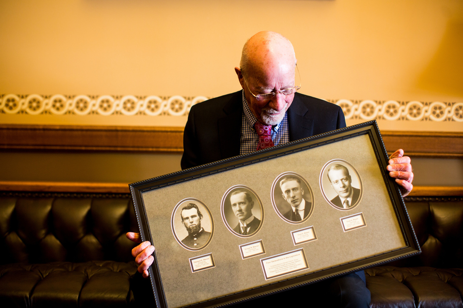 Risser holds a frame with photos of four generations of legislators in his family. His father, Fred E. Risser was a state senator; his grandfather, Ernest Warner, was an assembly member; and his great-grandfather, Clement Warner, was a state senator and assembly member following the Civil War. (Narayan Mahon for NPR)